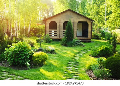 small wooden country house view in summer. Stone pathway, green lawn, conifers and shrubs. Garden design in english style.
