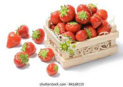 Small wooden crate full of strawberries over white
