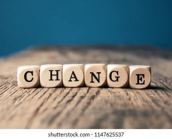 Small wooden dices with the word Change on an office table