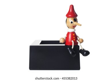 Small wooden doll of Pinocchio liar with big nose seated on a black box isolated on white background