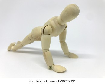 Small wooden dummy during push ups on white background.