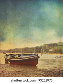 A small wooden ferry boat at low tide at Salcombe in Devon. A vintage or grunge style effect has been applied. set on a portrait format with room for copy above.