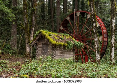 Small Wooden Hobbit Style House and Red Water Wheel in the Forest.