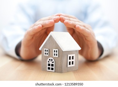Small wooden house covered by hands