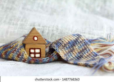 small wooden house with light in the windows is wrapped in a knitted scarf on a light background. insulated outside cozy inside