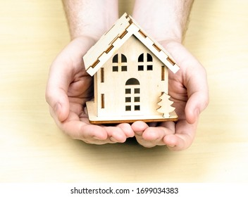 A small wooden house in male hands. The concept of buying, selling, renting real estate. Happiness at home
