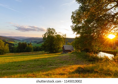 Small, wooden house with a panoramic view on the beautiful forest, alpine mountains and valleys and idyllic meadow fields of South Germany close to the Alpes with a blue sky before sunset