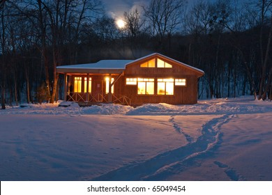 a small wooden house in a snowy forest