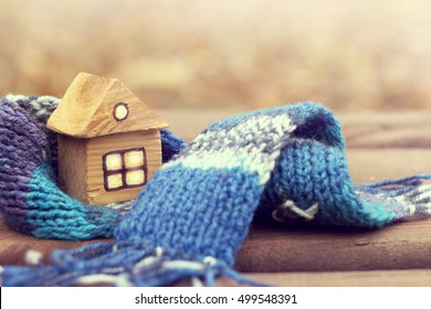 small wooden house in a warm blue scarf / property insurance