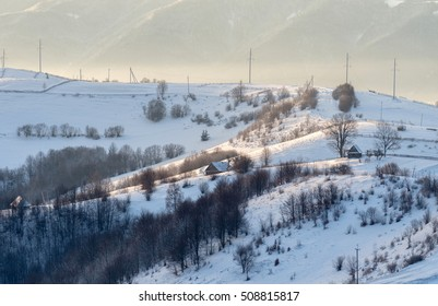 Small wooden houses on the hillside. Winter mountain landscape. At dawn.