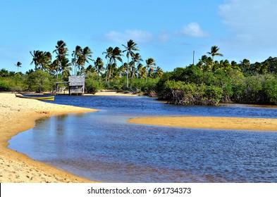 Small wooden hut on a Brazilian coast beach surrounded by the small river bank in Trancoso in the city of Porto Seguro, Bahia, Brazil.