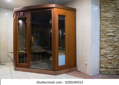 a small wooden infrarered sauna booth in a spa. Infrared Saina cabin in a small home Spa