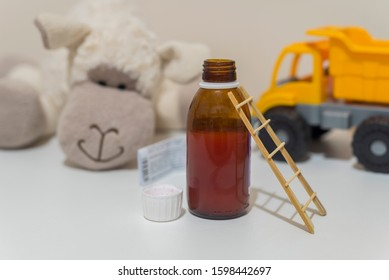 small wooden ladder.  prescription and medicine syrup. open bottle. with children toys in background. small wooden ladder. drug poisoning child