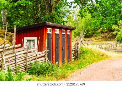Small wooden outhouse with four doors beside a country road. Stensjo village in Smaland, Sweden.