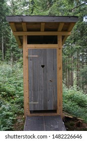 small wooden outhouse in the woods