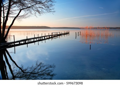 Small Wooden Pier by Calm Lake at Sunrise