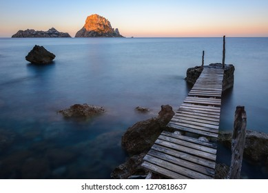 Small wooden pier in Cala d'Hort beach, Es Vedra as background, Ibiza island, Spain