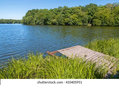 Small wooden pier at the shore of a forest lake