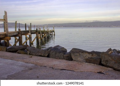 A small wooden pier used by the local yaucht club on The Esplanade at Holywood County Down. Belfast Lough and the distant County Antrim shore can be seen.