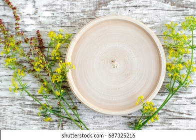Small wooden plate as a place for text and small field flowers on the white shabby wooden background. Herbarium, herbal medicine and botany concept. Top view, copy space.