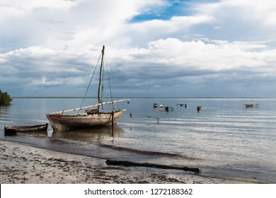 Small wooden sailboat on the water at the beach at sunrise in Mafia Island, Tanzania, with cloudy sky and calm water with surrounding dugout canoes.