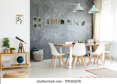Small wooden table with telescope, books and potted plants in modern dining room