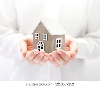 Small wooden toy house in hands