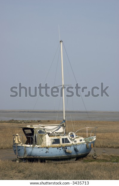 A small yacht in the mud at low tide