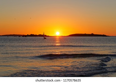 A small yacht sails back to shore on the Celtic Sea as the sun sets behind a group of small islands.