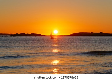 A small yacht sails on the Celtic Sea near Landeda, Brittany, as the sun sets between two small islands.