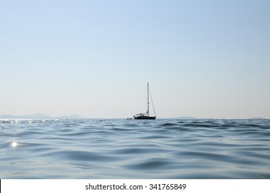 A small yatch in the middle of the sea in a clear sky day