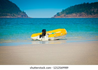 Small yellow boat on a sandy beach in front of turquoise ocean.