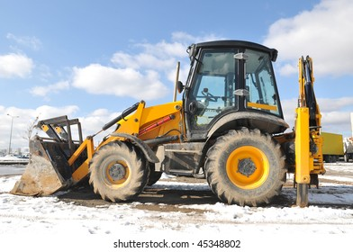 Small yellow bulldozer over cloudy sky