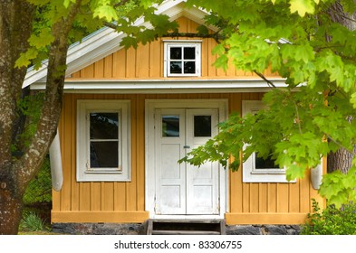 small yellow cabin with maples in front