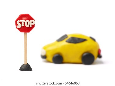 Small yellow car model from plasticine with stop road sign. Isolated on white. Close-up.