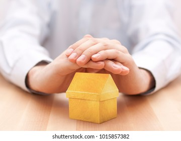 Small yellow house protected by hands