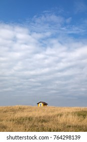Small yellow hut in long grass in Havre Aubert, Iles de la Madeleine, Canada. Big sky with space for your text