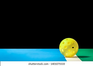 Small Yellow Pickleball... Yellow Pickleball on the boundry line of pickleball court and large background that can easily be remove and replaced.  Blue court area and green out of p
