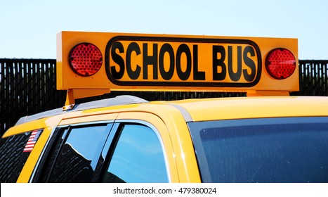 Small yellow school bus with sign on the top