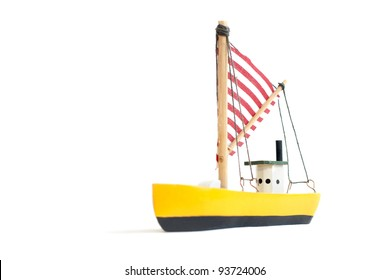 Small yellow toy sailing boat on white background