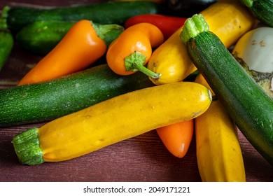 une petite courgette jaune en gros plan au milieu de petits légumes du jardin
