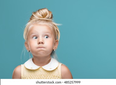 Small, young, funny girl, inflated cheeks on blue background