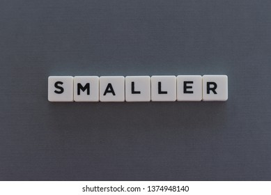 Smaller word made of square letter word on grey background.