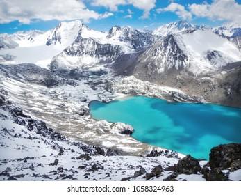 Smaragd water of misty Ala Kul lake in Terskey Alatoo mountains, Karakol national park, Kyrgyzstan