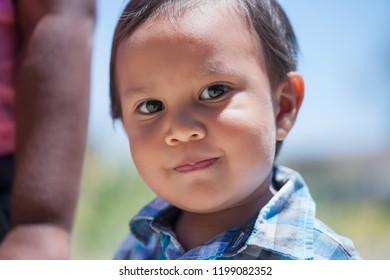 Smart 2 year old boy with bright eyes and cute smile looking innocent and standing next to sister in an outdoor park during summer