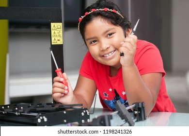 Smart 8 year old girl with tools in hand, ready to assemble a 3D printer with a positive attitude