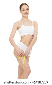Smart about her body. Attractive joyful woman measuring her body using a tape measure looking to the camera smiling on white background.