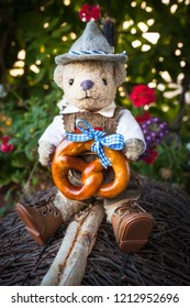 Smart, adorable teddy bear wearing german bavarian traditional costume leather pants and hat, delicious pretzel with blue ribbon in his hands, sitting at roof, natural dark background