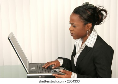 Smart african american business woman using laptop with phone in hand