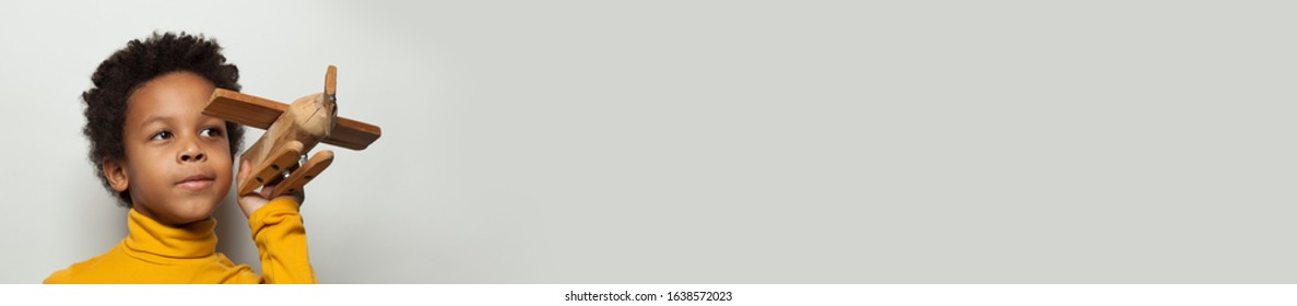 Smart African American child boy with plane model on white background